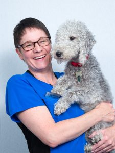 Claire Barker (Receptionist) Holding Fluffy Grey Dog